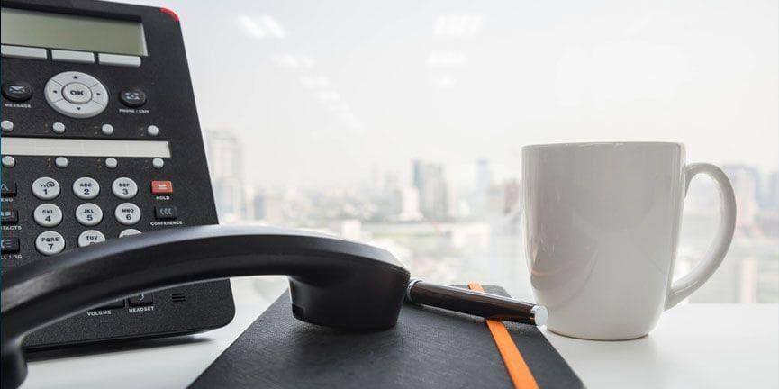 IP phone on office desk with notebook and coffee mug