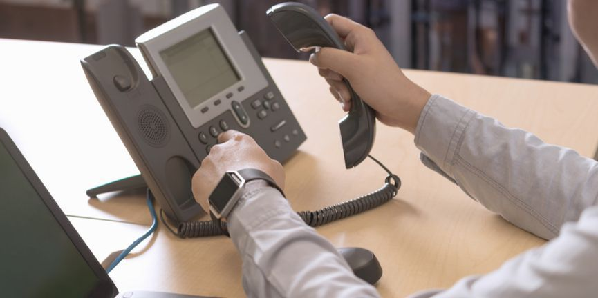 businessman dialing on ip desk phone