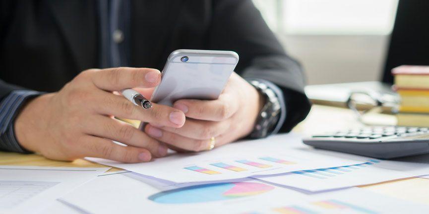businessman at desk on smartphone sending sms message