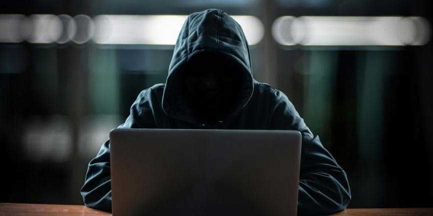 shadowed hacker using laptop computer