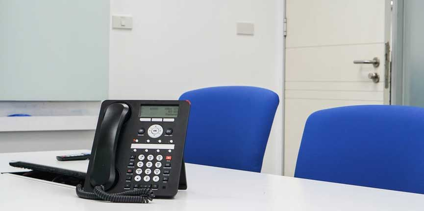 conference calling phone on desk in meeting room