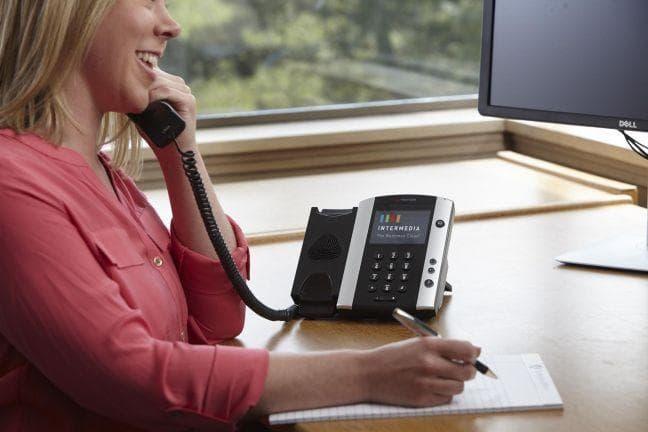 employee using Intermedia desk phone