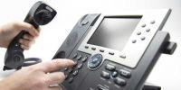 employee hand dialing keypad on IP phone
