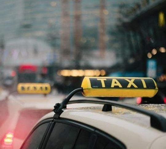 row of taxi cabs waiting for passengers