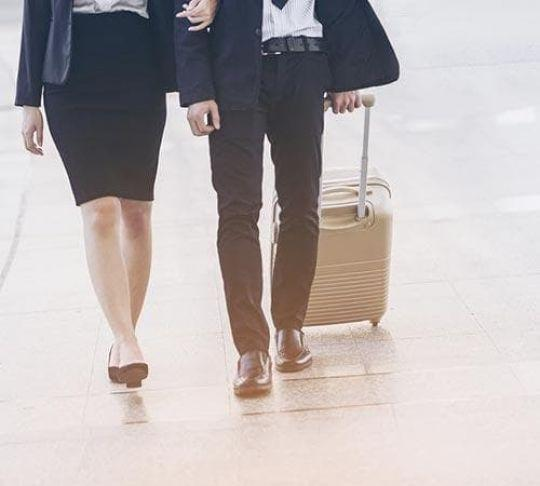 woman and man walking with suitcase