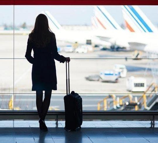 woman at airport traveling with suitcase
