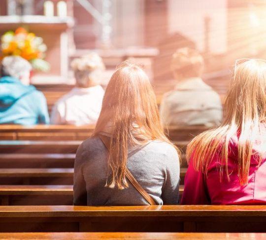 people kneeling in church pews