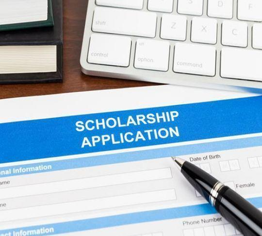 scholarship application form with pen and keyboard